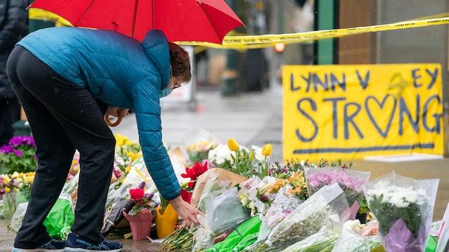Une dame portant un parapluie pose des fleurs sur le trottoir devant la bibliothèque Lynn Valley.