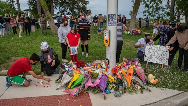 Des bouquets de fleurs empilés près d'un réverbère avec des gens assemblés qui se recueillent.