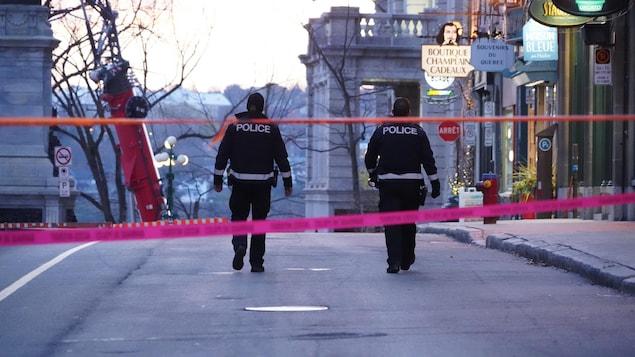 Deux policiers de dos dans la rue.