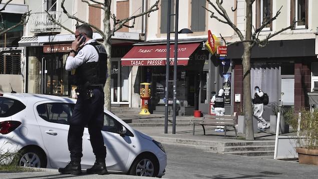 Un policier parle sur un portable à côté d'une voiture stationnée, devant des commerces.