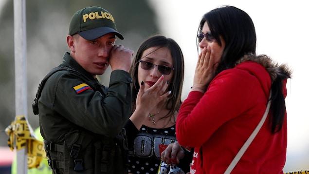 Un policier et deux femmes pleurent près du lieu de l'explosion, à Bogota, jeudi.