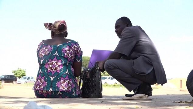 Un homme accroupi discute avec une femme.