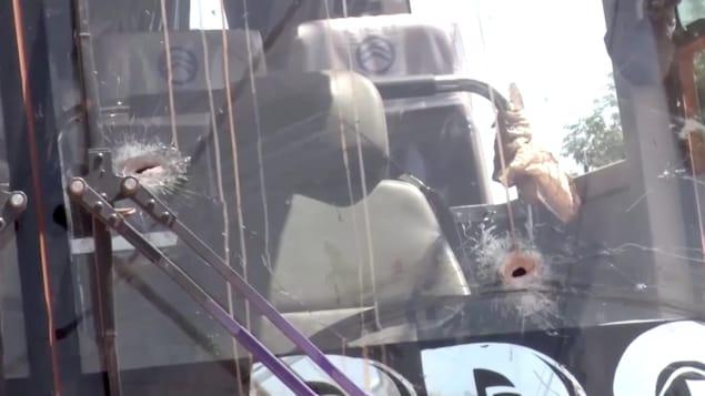 Deux trous de balle ont endommagé le pare-brise du véhicule.