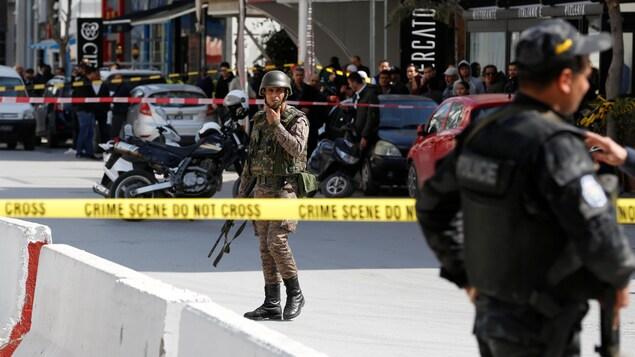 Un policier et un soldat marchent dans le périmètre de sécurité.