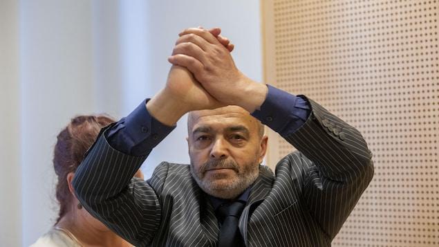 Le suspect Walid Abdulrahman Abu Zayed lève ses mains jointes au dessus de sa tête lors d'une comparution au tribunal d'Oslo, en Norvège.