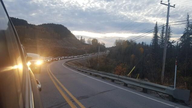Une longue file de plusieurs dizaines de voitures se dessine sur la route 138.