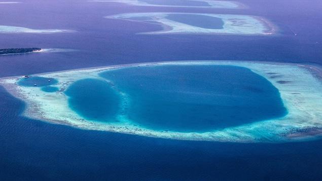 Photographie aérienne d'atolls des Maldives. Ils sont caractérisés par des couronnes de récifs coralliens entourant des lagons.