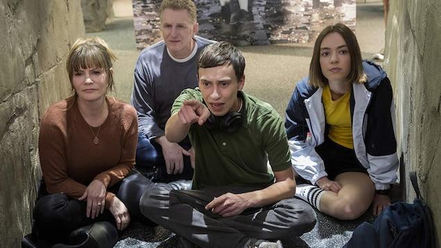 Les quatre personnes sont assises par terre et le jeune homme montre quelque chose du doigt.