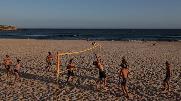 Des gens jouent au volleyball sur une plage de Sydney.