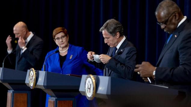 Quatre dirigeants politiques derrière des lutrins lors d'une conférence de presse.