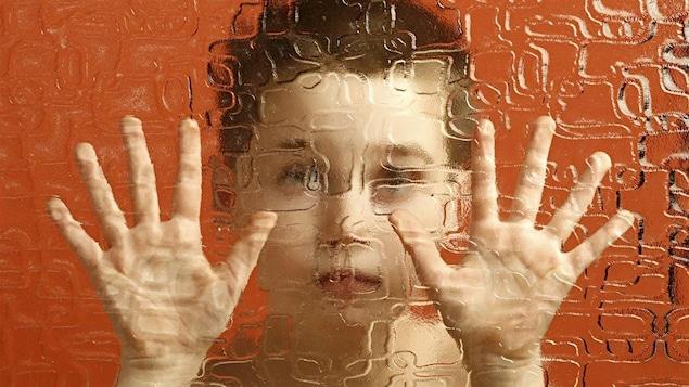 Un enfant prisonnier derrière une paroi translucide.