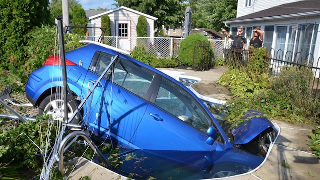 Un véhicule bleu dans une piscine creusée et 2 personnes regardent la scène.