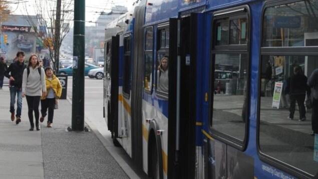 Des piétons s'approchent d'un autobus à l'arrêt dans le Grand Vancouver.