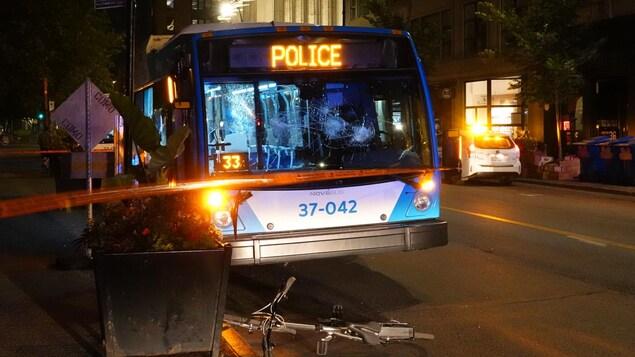 Un autobus aux fenêtres brisées est stationné en bordure de la rue.