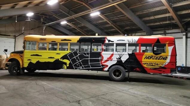 L'autobus peint stationné dans un garage.