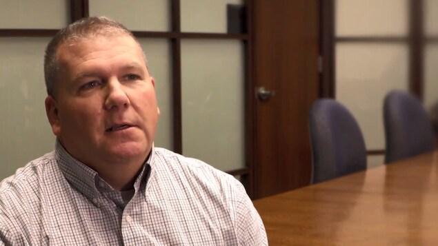 Richard Hetherington, portant une chemise à carreaux regarde le journaliste derrière la caméra lors d'une entrevue.
