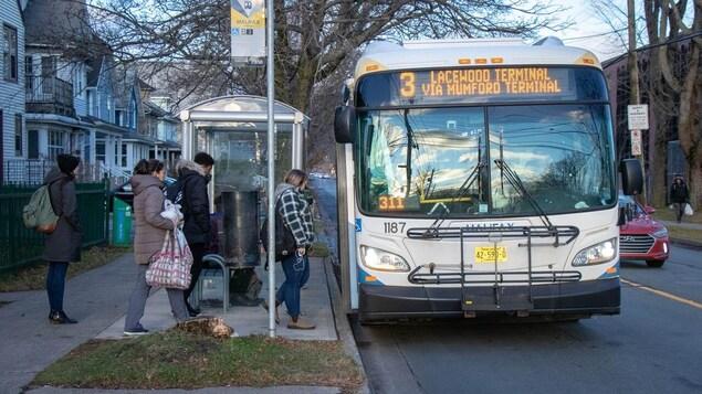 Un autobus à un arrêt dans une rue d'Halifax. quatre personnes sont sur le point d'embarquer à bord.