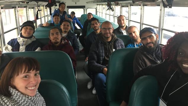 Des travailleurs étrangers sont rassemblés dans un autobus.