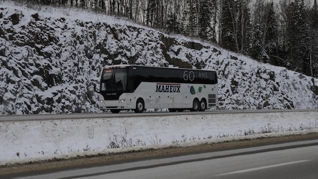 Un autobus de la compagnie Maheux roule sur la route 117 enneigée.