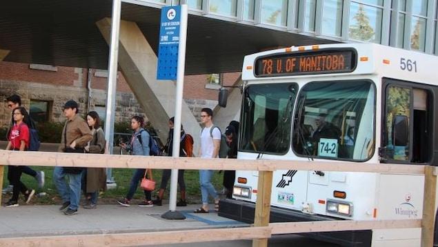 Un autobus blanc est garée. Des hommes et des femmes en descendent.