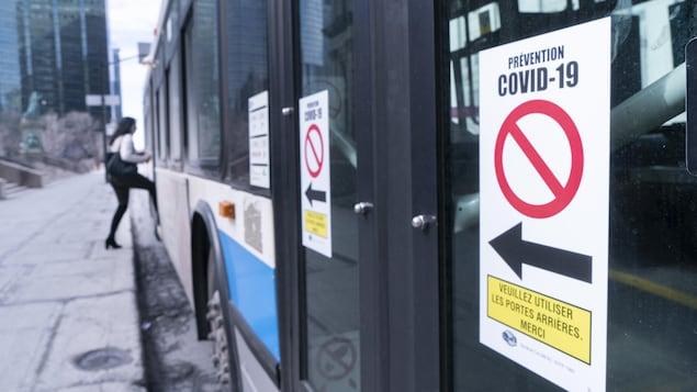 Une pancarte sur la porte avant d'un autobus demande aux usagers d'« utiliser les portes arrières ».