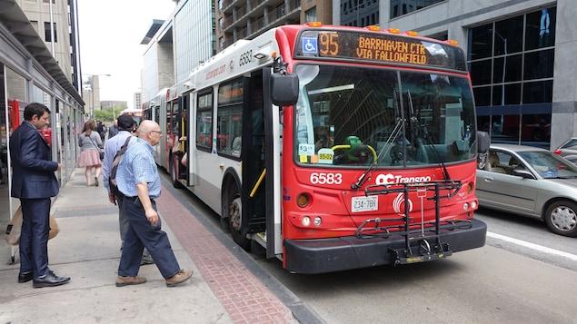 Des passagers montent à bord d'un autobus d'OC Transpo.