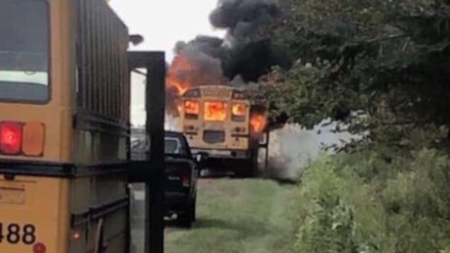 Un autobus scolaire est immobilisé sur le bord de la route et des flammes sont visibles à travers les fenêtres.