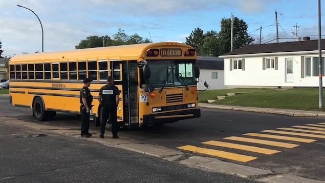 Deux policiers embarquent dans un autobus scolaire