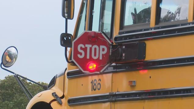 Un autobus scolaire a déployé son panneau d'arrêt destiné aux automobilistes.