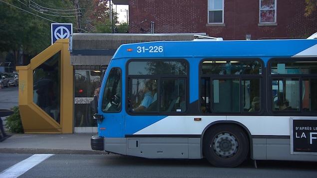 Un autobus arrêté à une station de métro du réseau de la STM, à Montréal. On voit le logo du métro de Montréal derrière l'entrée de la station.