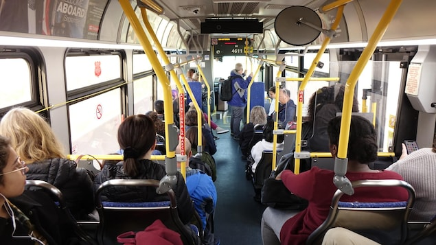 Des gens debout dans un autobus.