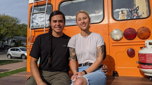 Shanny Kirby et Karlen Janiver sint assis sur une plateforme à l'arrière de leur autobus.
