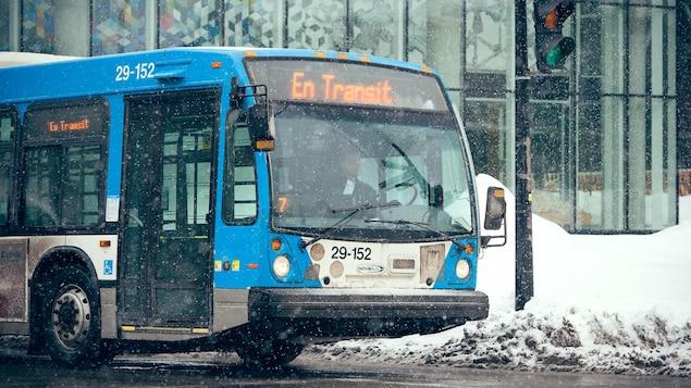 Un autobus de la STM est en transit au centre-ville de Montréal, sous la neige.