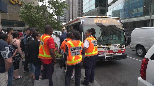 Photo de superviseurs portant un dossard orange et d'usagers qui attendent de monter à bord d'un autobus.