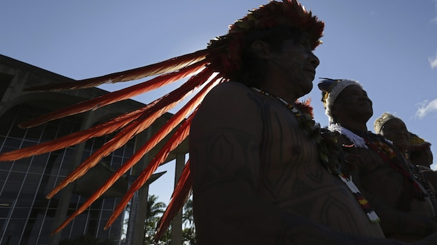 Des hommes autochtones du Brésil en habits traditionnels.