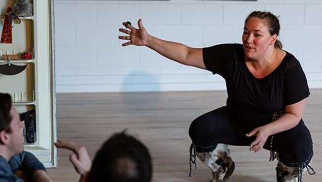 L'artiste est habillée de noir avec des bottes en peau. Elle est accroupie et dialogue avec deux autres personnes.