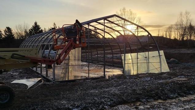 Une serre en construction avec un coucher de soleil en arrière plan.
