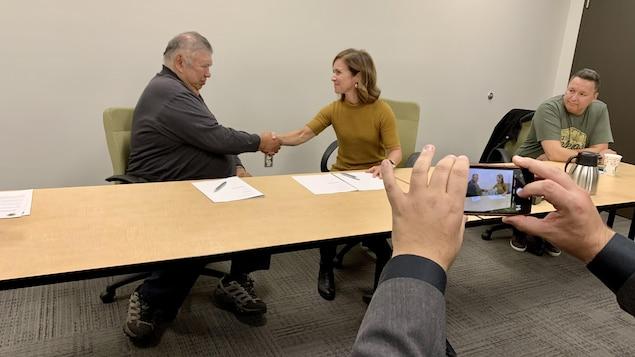 François Neashit serre la main de Julie Boucher lors de la conférence de presse.