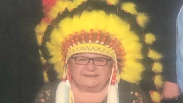 L'ex-cheffe de la Première Nation d'Okanese, Marie-Anne Day Walker-Pelletier avec une coiffe autochtone sur la tête.