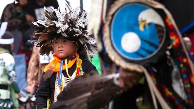 Un enfant porte un habit traditionnel autochtone.
