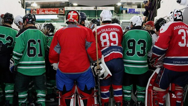 Des hockeyeurs autochtones de dos avant de sauter sur la glace.