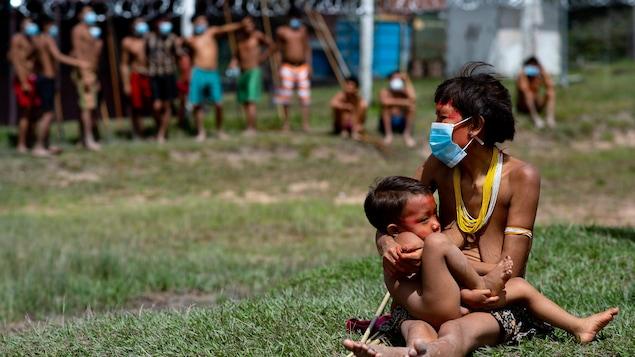 Une mère autochtone allaite son bébé et elle porte un masque sanitaire.