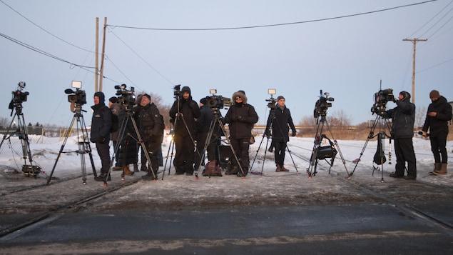 Des professionnels des médias en face de manifestants autochtones qui bloquent la voie ferrée du CN à Saint-Lambert.