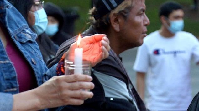 Une femme tient une bougie lors d'une veillée à Calgary à la mémoire des vitimes des pensionnats pour autochtones.