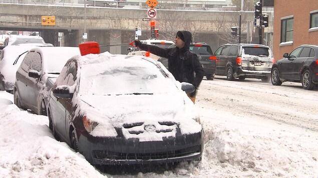 Un homme enlève la neige sur le toit d'une voiture avec une petite pelle.