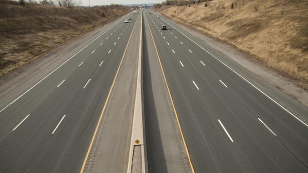 Des véhicules circulent au loin sur l'autoroute à péage.