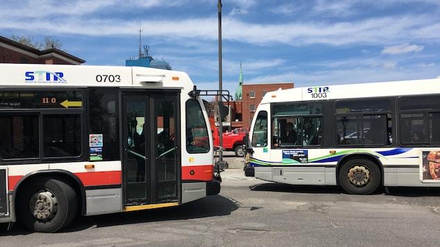 Deux autobus face à face au terminus du centre-ville de Trois-Rivières.