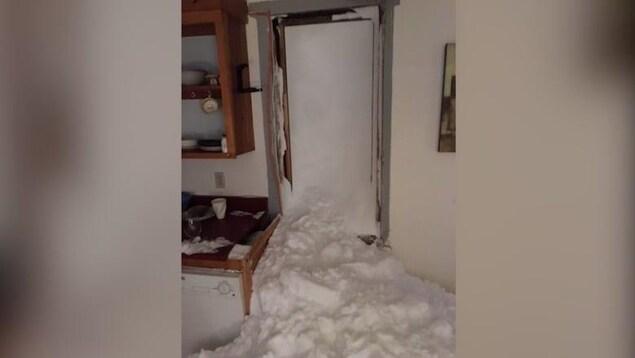 Une maison envahie de neige.