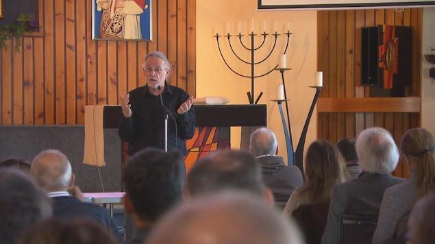 L'historien René Beaudoin est à un micro et parle devant une dizaine de personnes dans une église.