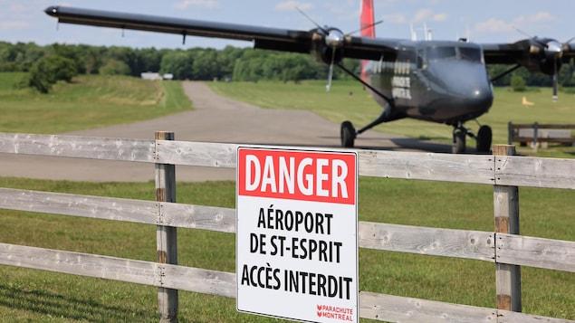 Un petit avion derrière une clôture où est apposée une pancarte disant : « Danger, aéroport de St-Esprit, accès interdit ».